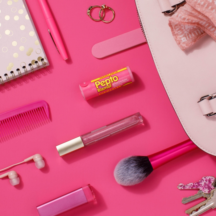 Pepto bismol chewable on pink flatlay purse items - p&g product photography