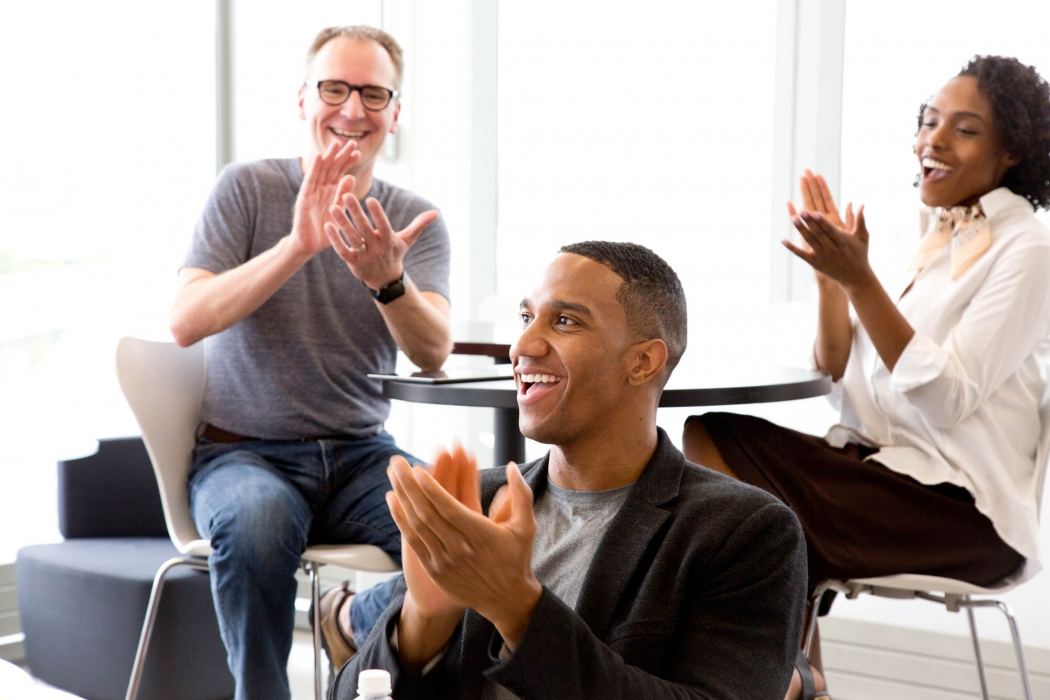 workplace photography of employees clapping and being happy p&g