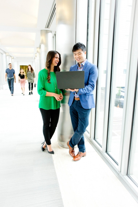 two professionals look at a laptop in common space at a p&g - workplace photography