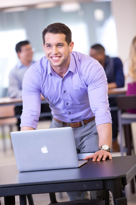 man smiles and stands over laptop at p&g - workplace photography
