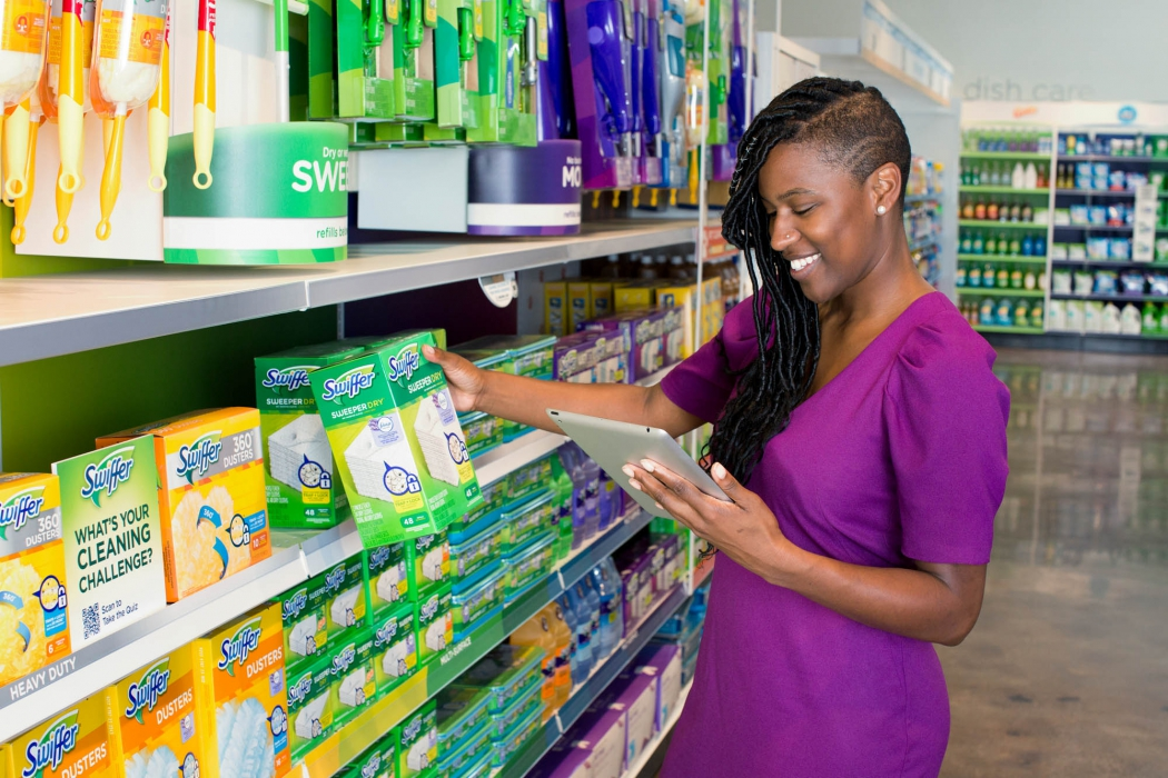 woman with Ipad reaches for swiffer product at p&g shelf mock up - workplace photography
