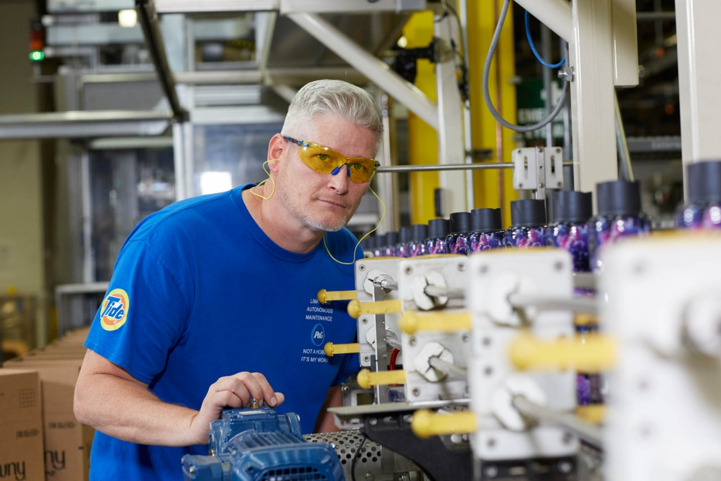 a man inspects the process line at a p&g plant - workplace photography