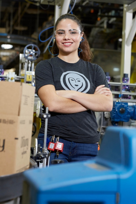 woman smiles with arms crossed at p&g plant - workplace photography