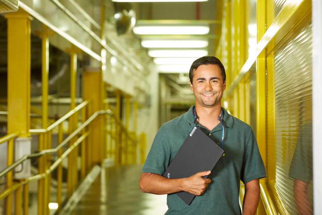 smiling man holding laptop in industrial hallway - p&g workplace photography