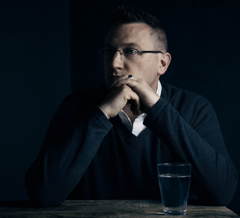 portrait of a man at a table with glass of water - portrait photography