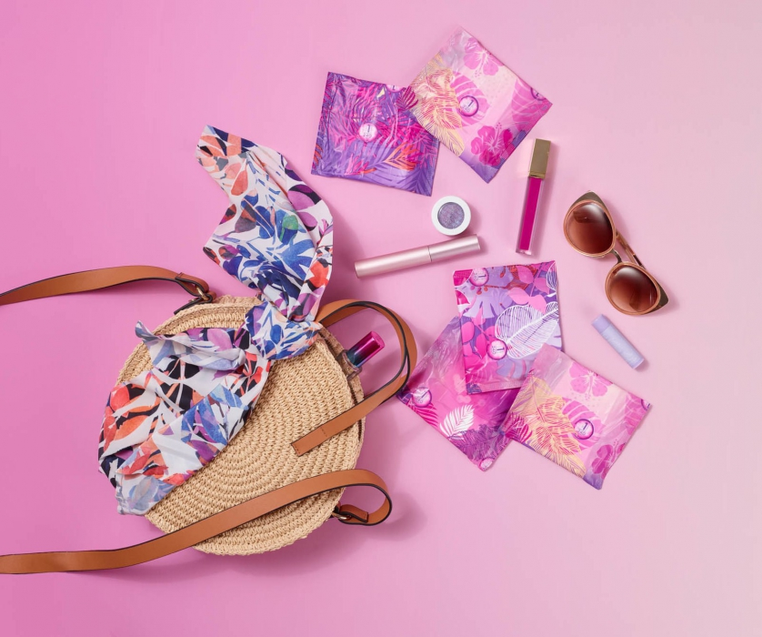 Purse spilling pads and items on gradient - p&g product photography