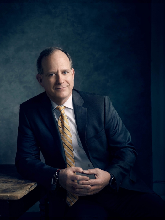 Portrait of a corporate professional at a table with a blue background - portrait photography
