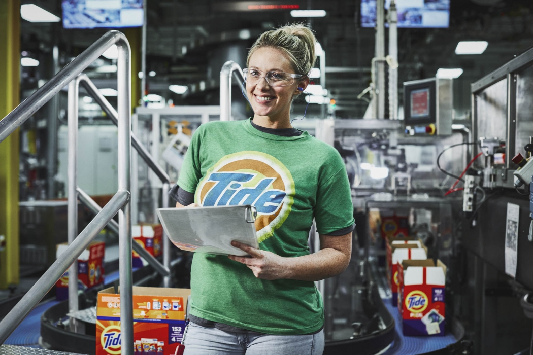 A Happy woman wearing tide shirt working at industrial P&G plant - Workplace Photography
