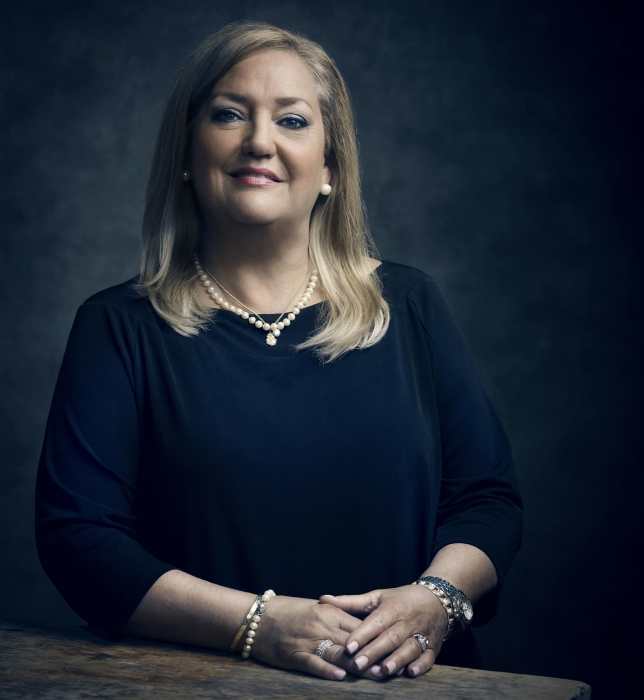 Portrait of a pofessional woman at a table on with a dark background - Portrait photography